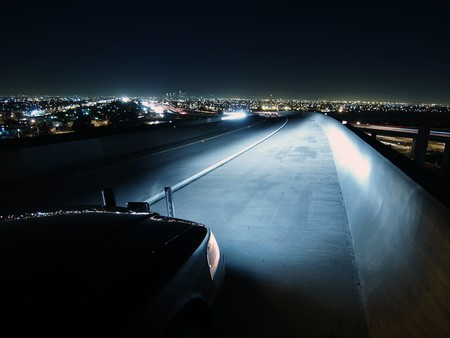 freeway: A police car at work at night on a highway bridge.