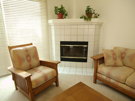 A fireplace, chair and sofa inside a California Townhouse. Stock Photo - 4854824