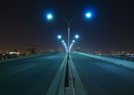city lights: Empty bridge, towers and street lights at night. Stock Photo