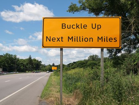 million: Buckle Up Next Million Miles highway sign.