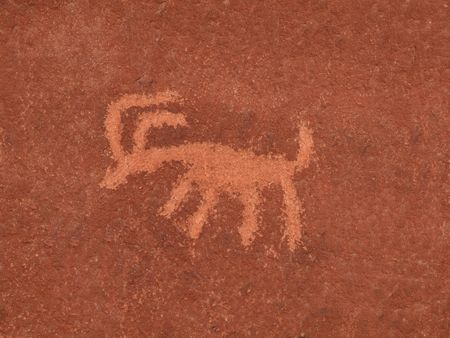 Ancient American Indian petroglyph on a red sandstone wall. photo