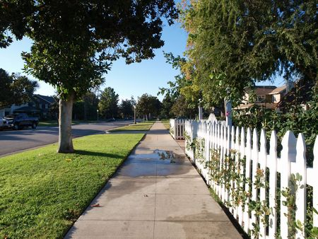 white picket fence: Picket fence on a pretty middle class street.
