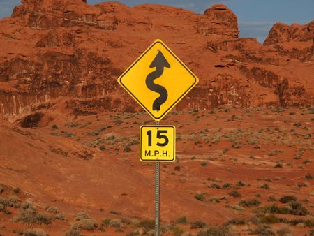 Desert curves ahead highway sign with cliff backdrop. Stock Photo - 5705757