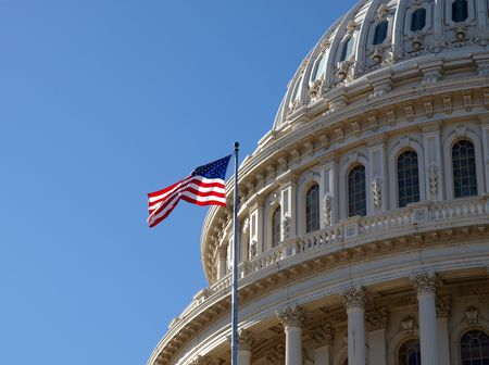 The United States Capitol dome and flag in Washington DC. 免版税图像