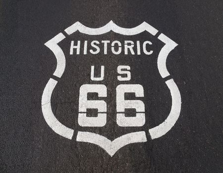 Historic US Route 66 pavement road sign in California's Mojave desert. Imagens