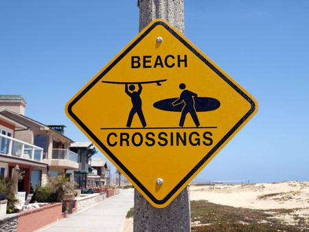 Beach crossing warning sign along a busy Southern California bike route.