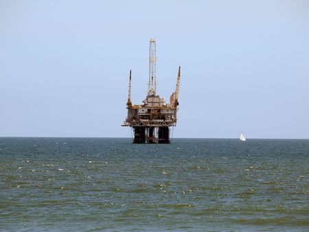 A sail boat passes a large offshore oil rig.   Stock Photo