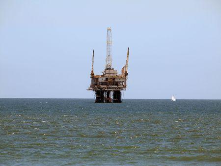 A sail boat passes a large offshore oil rig.   Banque d'images
