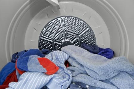 machine � laver: Guy v�tements et les serviettes dans la s�cheuse.   Fra�che, propre et pr�t � plier.
