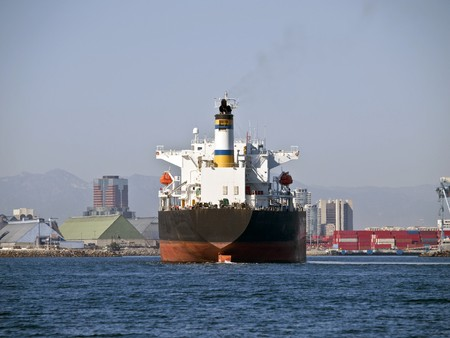 container port: Giant oil tanker cruises towards Long Beach California in warm afternoon light..