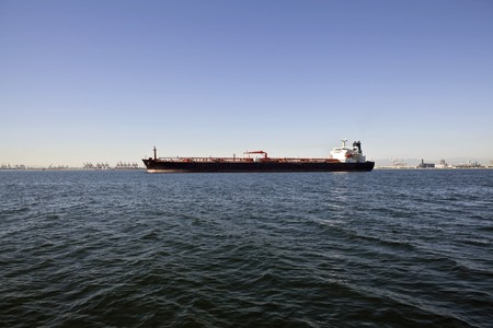 anchored: Large oil tanker anchored in a wide industrial harbor.