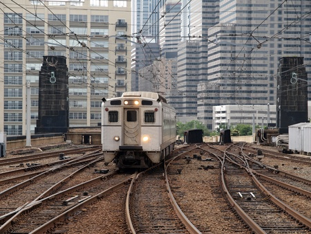 Urban passenger train with dense cityscape background.