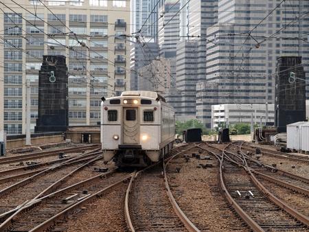 Urban passenger train with dense cityscape background.