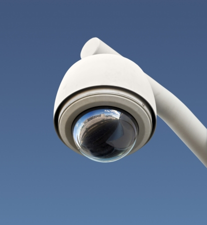 video surveillance: High tech overhead security camera with a gradient blue sky.