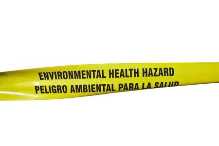 hazard tape: Environmental Health Hazard warning tape on a chain link fence.