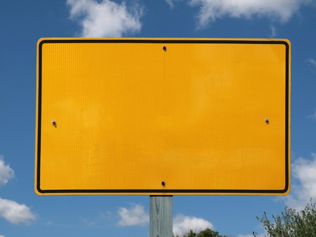 Blank reflective yellow highway message sign with puffy clouds. photo
