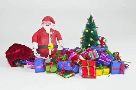 Clay Santa Figurine with piles of Miniature Gifts. Stock Photo - 9887760