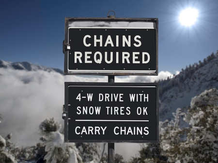 Chains or snow tires required sign with mountain backdrop. photo