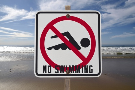 No swimming sign with Pacific ocean surf. Stock Photo - 10064873