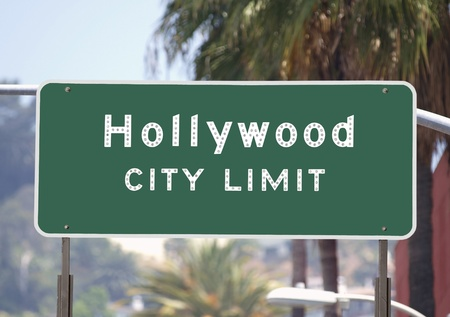 Hollywood city limits sign with palm trees.   photo