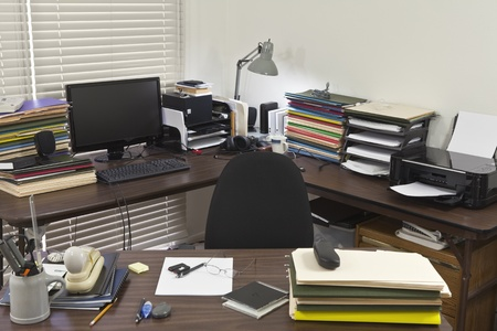 Busy, messy corner office with piles of files. photo