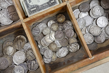 Vintage coins inside a old cash register drawer.