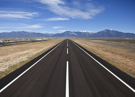 Rural county airport runway with snowcapped Rocky Mountain backdrop.