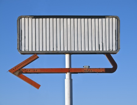 roadsides: Blank vintage arrow sign in early morning light.