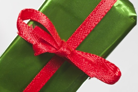 Miniature gift with bright red ribbon bow macro close up. Stock Photo - 13419099