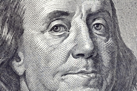 Macro close up of Ben Franklins face on the US $100 dollar bill.