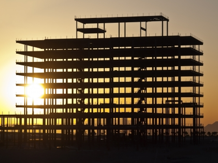Sunrise glowing through steel girder construction.  Stock Photo - 13629022