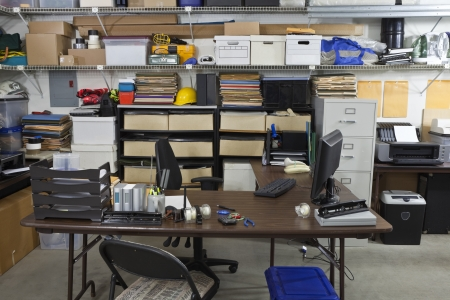 Untidy shop space office with boxes, files and clutter photo