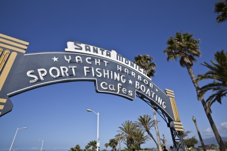 spent: SANTA MONICA, CALIFORNIA - May 26:  Historic Santa Monica pier entrance sign.  Santa Monica convention and visitors bureau says over one billion dollars are spent by visitors annaully.