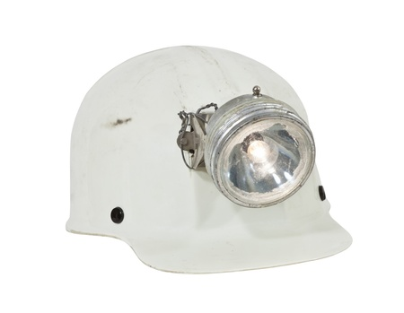 grungy isolated: Vintage caving and mining hard hat with lamp