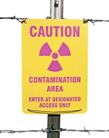 Caution radioactive contamination warning sign with barb wire fence isolated. photo