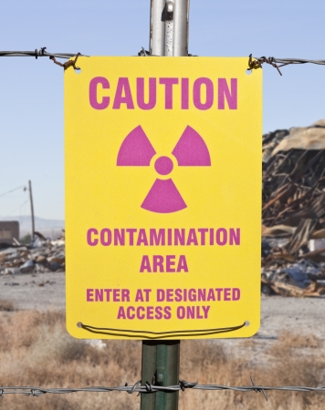 Caution radioactive contamination warning sign with barb wire fence. photo
