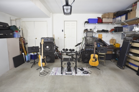 untidy: Rock band music equipment in a cluttered suburban garage.
