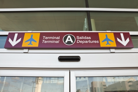 Overhead airport terminal spanish, english departure sign.