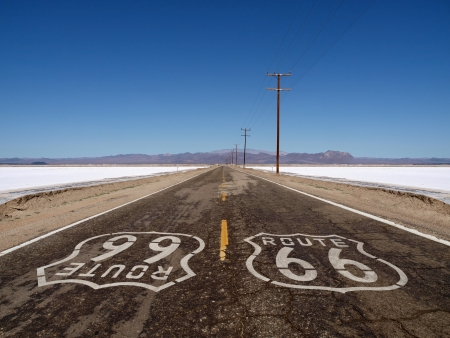 Route 66 sign painted on rough Mojave desert salt flat highway pavement. photo