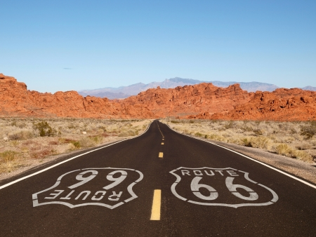 Route 66 pavement sign with Mojave desert red rock mountains. photo