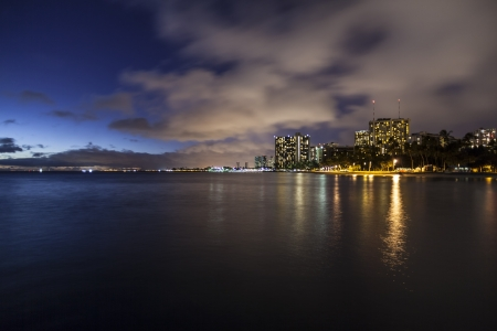 Night view towards downtown Honolulu from Waikiki beach in Hawaii  photo