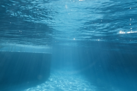 Underwater swimming pool ledge with sunbeam patterns. Banco de Imagens