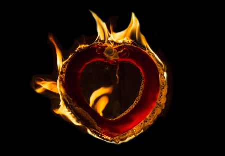 Burning love flaming fire heart with black background Stock Photo - 17180483