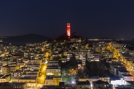 coit tower: Editorial night view of Coit tower with colorful holiday lighting.