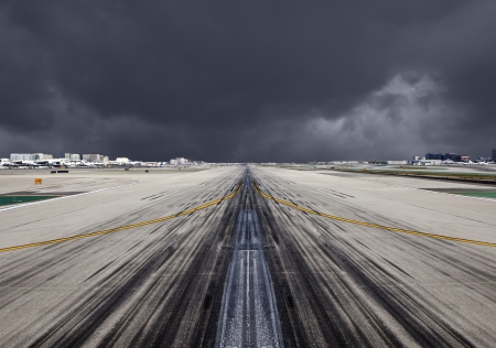 off ramp: Airport Runway with severe storm clouds  Stock Photo