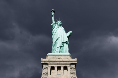 dark clouds: An upshot of the statue of liberty with thunderstorm.