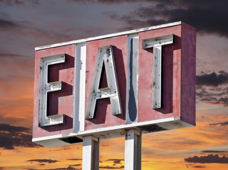 Retro faded eat sign with sunset sky.