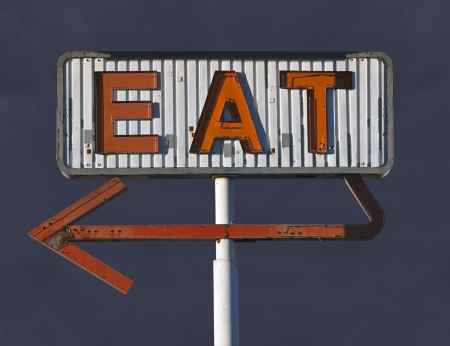 old sign: Vintage eat arrow sign in with dark storm sky