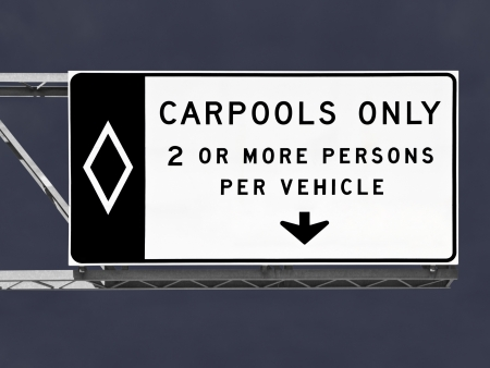Overhead freeway carpool only sign with storm sky. Stockfoto