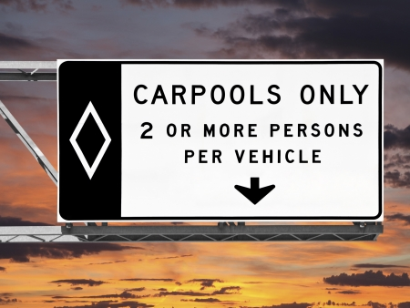 Overhead freeway carpool only sign with sunset sky.
